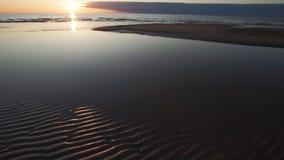 Hochroter Sonnenuntergang mit klarem Himmel und Spiegel wie Reflexionen im wasser- gewellten Sand und in den Wellen - tuja, Lettl stock video footage