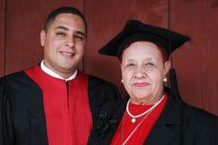 Hochschulabsolvent in den Roben mit seiner Großmutter. lizenzfreies stockbild