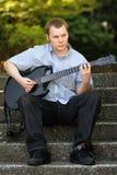 Hochschuljugendlicher mit Gitarre Stockfoto