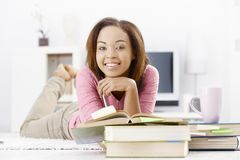 Hochschulmädchen, das auf Fußboden studiert Stockbilder