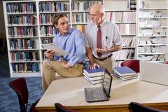 Hochschulprofessor mit dem Kursteilnehmer, der in der Bibliothek spricht Stockfotografie
