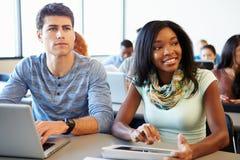 Hochschulstudenten, die Digital-Tablet und -laptop in der Klasse verwenden lizenzfreie stockbilder