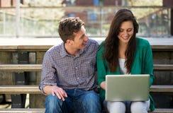 Hochschulstudenten, die draußen an Laptop arbeiten Stockfotografie