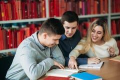 Hochschulstudenten, die zusammen bei Tisch mit Büchern und Laptop sitzen Die glücklichen jungen Leute, die Gruppe tun, studieren  lizenzfreies stockbild