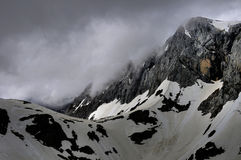 Hochschwab mountain. Hidden in the clouds with avalanche area beneath rocky wall Royalty Free Stock Photos