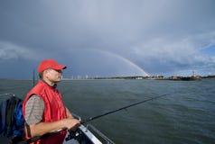 Hochseefischerei und glücklicher Regenbogen Stockfotos