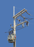 Hochspannungs-Pole mit dem Transformator lokalisiert auf blauem Hintergrund Lizenzfreies Stockfoto