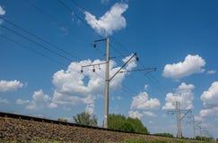 Hochspannungsdraht entlang Eisenbahn unter blauem Himmel Stockfoto