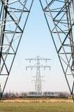 Hochspannungsenergiebeiträge in der Landschaft Stockfotos