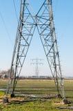 Hochspannungsenergiebeiträge in der Landschaft Stockbild