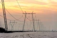 Hochspannungsenergiefreileitungsmaste im Sonnenuntergang Stockfotografie