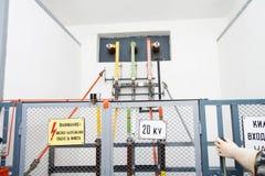 Hochspannungsequipement mit einem Zaun, Warnzeichen und einer Hand   Lizenzfreies Stockbild