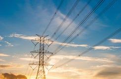 Hochspannungsfernleitungen auf orange und blauem Himmel, Sonnenaufgang Lizenzfreie Stockfotografie