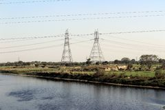 Hochspannungsfreileitungsmaste nähern sich Fluss Yamuna Stockfoto