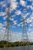 Hochspannungskraftübertragungzeilen und -gondelstiele Stockfotos