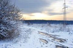 Hochspannungsleitungen bei Sonnenaufgang in einem Winter Schlechte schlammige Winterstraße Schönes Bild des Winters landscape Lizenzfreie Stockfotos