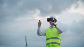 Hochspannungsleitungen gesteuert von einem männlichen Ingenieur unter Verwendung der virtuellen Realität, um Macht zu steuern Alt stock video