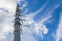 Hochspannungsleitungen und Isolatoren über Hintergrund des blauen Himmels Lizenzfreie Stockbilder