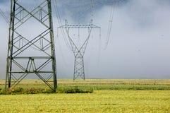 Hochspannungsmast des großen Stroms mit Stromleitungen Stockbild