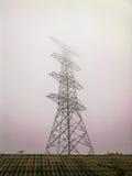 Hochspannungsstrompylonmorgens Nebel stockbilder