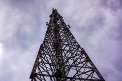 Hochspannungsturm gegen grauen Himmel mit Heben bewölkt sich Stockfotografie