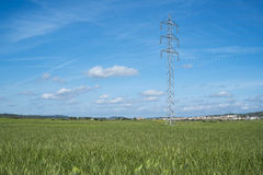Hochspannungsturm und Kabelleitung in der Landschaft unter einem blauen Himmel Lizenzfreie Stockfotografie