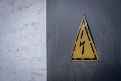 Hochspannungszeichen auf einem grauen Schild gegen eine weiße Backsteinmauer Lizenzfreies Stockfoto