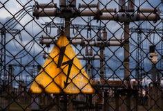 Hochspannungszeichen auf einem Hintergrund von Stromleitungen Beschneidungspfad eingeschlossen Stockfotos