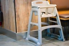 Hochstuhlsitz f?r sitzen, Position f?r Kinder im Schnellimbi? essend Gebrauchsbaby-Stuhlsitz f?r sicheres nettes Kind in Caf? bre lizenzfreie stockfotos