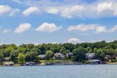 Hochwertige Häuser mit den Bootsdocks errichtet entlang dem Rand von einem See mit hohen grünen Bäumen unter einem blauen Himmel  stockbild