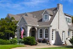 Hochwertiges graues Ziegelsteinhaus mit mehrfachen Giebeln und Kamin und Landschaftsgestaltung und Blumen und amerikanische Flagg lizenzfreie stockbilder