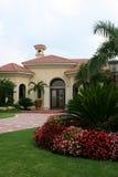 Hochwertiges Haus mit Flowerbed und tropischem Laub stockbild