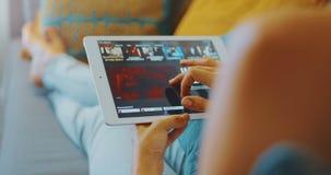 Hochwertiges 4k 12bit-Bildmaterial Frauen, die Netflix-App auf einem weißen Tablettengerät verwenden, während sie auf dem Sofa im stock video