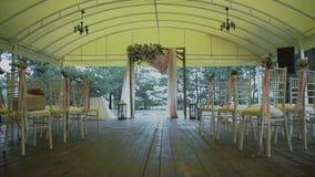 Hochzeit Arck verziert mit Blumen/Frau verziert einen Hochzeitsbogen mit Blumen/verziertem Platz für Hochzeitszeremonie stock video