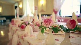 hochzeit bankett Die Stühle und die Tabelle für Gäste, verziert mit Kerzen, gedient mit Tischbesteck und Tonware und bedeckt stock footage