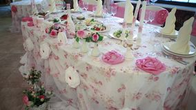 hochzeit bankett Die Stühle und die Tabelle für Gäste, verziert mit Kerzen, gedient mit Tischbesteck und Tonware und bedeckt stock video
