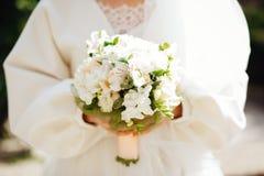 Hochzeit floristry in den Händen der Braut lizenzfreie stockbilder