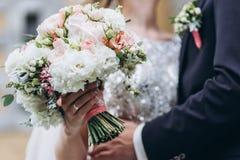 Hochzeit floristry in den H?nden der Braut lizenzfreie stockfotos