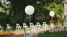 Hochzeit gegründet im Garten, Park Äußere Hochzeitszeremonie, Feier Hochzeits-Gang-Dekor Reihen von weißem hölzernem leeren sich stock video footage