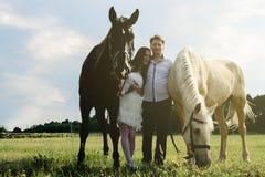 Hochzeit von glücklichen nahen Pferden der ungewöhnlichen Paare Stockfotografie
