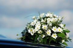 Hochzeits-Blumenstrauß auf einem schwarzen Auto Stockbilder