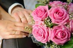Hochzeits-Blumenstrauß mit den Händen und den Ringen Stockfotos