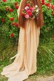 Hochzeits-Fotografie: Eine Braut in einem Seidenhochzeitskleid, das ein schönes großes Weiß hält, erröten, zacken, Pfirsich, purp lizenzfreies stockbild