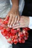 Hochzeits-Hände und Ringe auf Blumenstrauß Stockbild