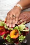Hochzeits-Hände und Ringe auf tropischem Blumenstrauß Stockfotografie