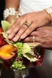 Hochzeits-Hände und Ringe auf tropischem Blumenstrauß Lizenzfreies Stockfoto