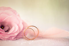 Hochzeits-Hintergrund mit Goldringen und schönem Eustoma stieg f Stockbild