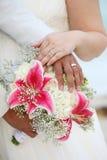 Hochzeits-Hände und Ringe auf dem Blumenstrauß - tropisch Stockfotos