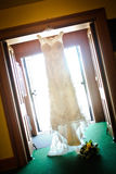Hochzeits-Kleid, das im Eingang hängt Lizenzfreies Stockfoto