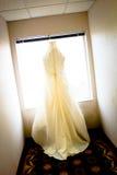 Hochzeits-Kleid, das im Fenster hängt Lizenzfreie Stockfotografie